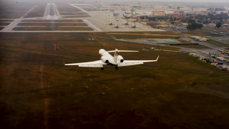 Aerial-Of-A-Private-Jet-Landing-At-An-Airport-From-Behind