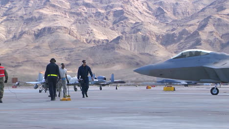 Maintenance-Workers-On-An-Air-Force-Runway-With-F15-And-F16-Jet-Fighters-In-Background