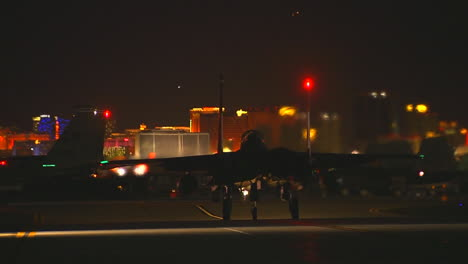 F15-Fighter-Jets-Taxis-On-A-Runway-At-Night-Against-The-Las-Vegas-Skyline