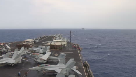 High-Angle-Shot-Across-The-Deck-Of-An-Aircraft-Carrier-At-Sea