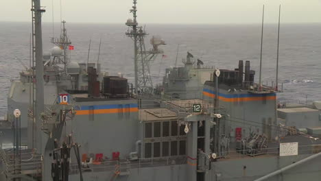 Three-Navy-Ships-Travel-Alongside-One-Another-During-A-Replenishment-At-Sea-Exercise