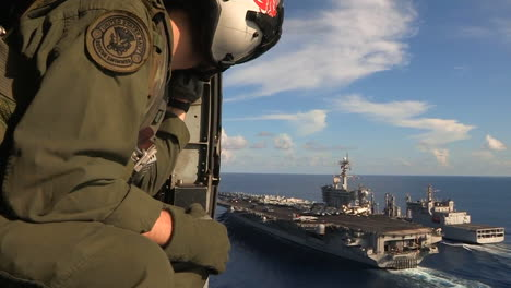 Aerial-From-A-Helicopter-With-Military-Personnel-Visible-Over-An-Aircraft-Carrier-As-Sea