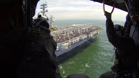Aerial-From-A-Helicopter-With-Military-Personnel-Visible-Over-An-Aircraft-Carrier-As-Sea-1