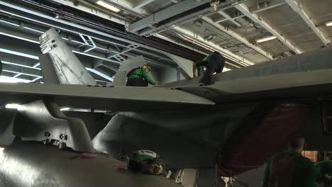 Men-And-Women-Work-On-Aircraft-Inside-A-Hangar-On-An-Aircraft-Carrier