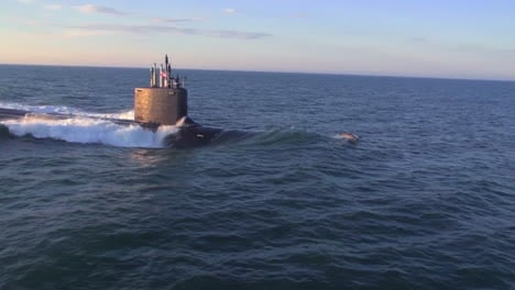Antenas-Sobre-Un-Submarino-En-El-Mar-Con-Delfines-Saltando-A-Través-De-La-Proa