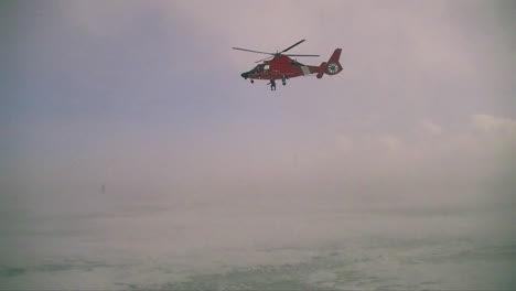 An-Airman-Descends-From-A-Coast-Guard-Search-And-Rescue-Helicopter-In-A-Blizzard-1