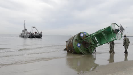 A-Coast-Guard-Barge-Drags-A-Buoy-Off-A-Beach-After-A-Storm