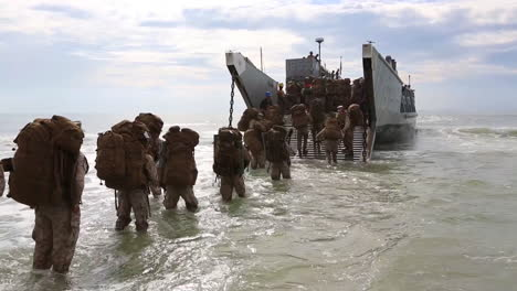 Troops-Wade-Through-Ocean-Waves-To-Board-An-Amphibious-Transport-Vehicle