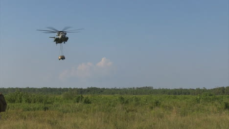 The-Sikorsky-Ch53-Helicopter-Lifts-And-Drops-A-Humvee-In-A-Field
