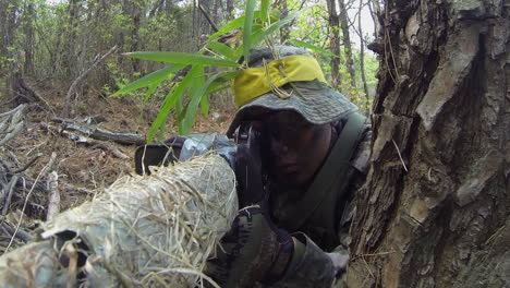 Camouflaged-Sniper-Aims-Gun-From-Forest-Hideout-Position