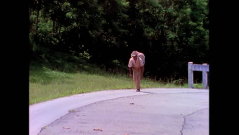 An-old-man-carries-tobacco-along-a-road-in-the-1980s