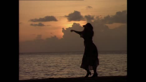 A-sexy-woman-dances-in-front-of-the-sunset-in-a-Latin-American-country-Cuba-in-the-1980s-1
