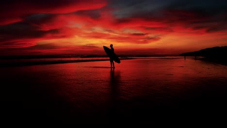 Beautiful-Aerial-Of-A-Surfer-Standing-With-Surfboard-In-Gorgeous-Dusk-Sunset-Red-Light