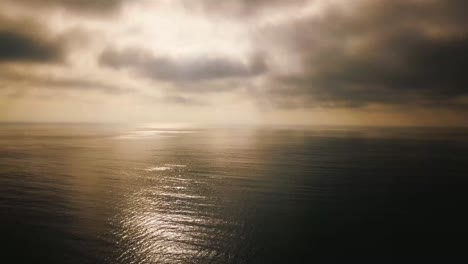 Aerial-Over-Fog-On-A-Golden-Calm-Ocean-Scene-Suggests-Inspiration-And-Wonder