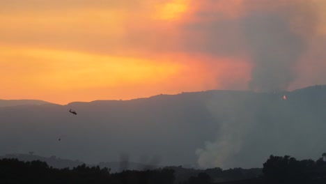 The-Thomas-Fire-Burns-At-Sunset-In-The-Hills-Above-Ojai-California-With-Water-Dropping-Helicopter-Passing-1