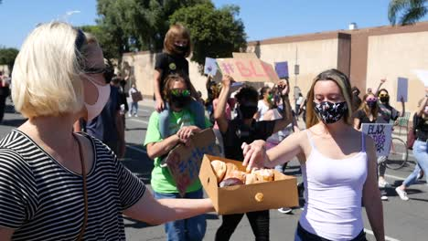 Extreme-Slo-Mo-Woman-Offers-Donuts-To-Marching-Protesters-During-A-Black-Lives-Matter-Blm-Parade-In-Ventura-California