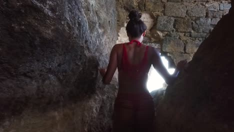 A-Beautiful-Woman-Walks-Through-A-Cave-In-Barbados-Caribbean