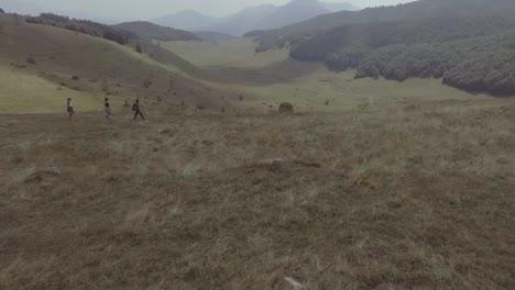 Antena-De-Drone-De-Tres-Excursionistas-Caminando-Sobre-La-Aldea-De-Lukomir-Highlands-Y-Montañas-De-Bosnia-Y-Herzegovina-Europa-Oriental