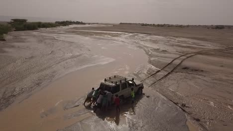Aerial-Of-People-Pushing-A-4X4-Jeep-Out-Of-A-Muddy-River-In-The-Deserts-Of-Djibouti-Or-Somalia-Africa