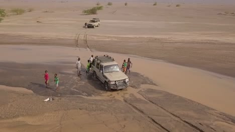 Aerial-Of-People-Pushing-A-4X4-Jeep-Out-Of-A-Muddy-River-In-The-Deserts-Of-Djibouti-Or-Somalia-Africa-1