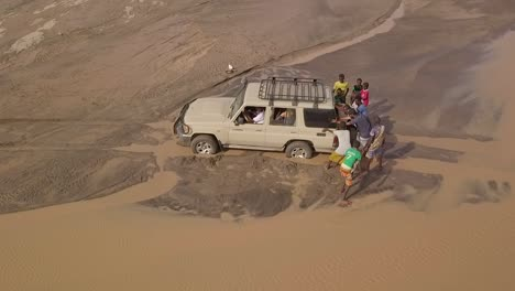 Aerial-Of-People-Pushing-A-4X4-Jeep-Out-Of-A-Muddy-River-In-The-Deserts-Of-Djibouti-Or-Somalia-Africa-2