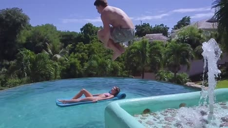 Super-Slow-Motion-Shot-Of-A-Man-Doing-A-Cannonball-Dive-Into-A-Pool-And-Upsetting-A-Woman-Floating-There