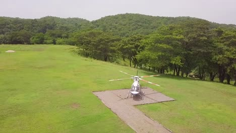 Good-Drone-Aerial-Of-A-Helicopter-On-A-Landing-Pad-In-A-Tropical-Jungle-Setting