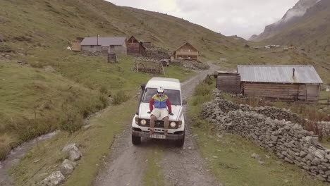 Vista-Aérea-Shot-Of-A-Man-With-A-Helmet-Riding-On-The-Front-Of-A-Jeep-Through-A-Village-In-Kosovo