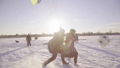 Two-People-Paraglide-On-A-Snowy-Field-In-Latvia