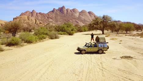 Aerial-Over-A-Man-Standing-On-A-4Wd-Safari-Camper-Van-Taking-Photos-Of-Rock-Formations-At-Spitzkoppe-Namibia-Africa