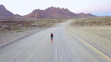 Aerial-Over-A-Woman-Running-On-A-Dirt-Road-Near-Spitzkoppe-Namibia