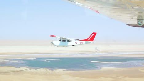 Slow-Motion-Air-To-Air-Shot-Of-A-Light-Plane-Flying-Over-The-Namib-Desert-Skeleton-Coast-Namibia