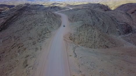 Excellent-Aerial-Of-A-4X4-Jeep-Safari-Vehicle-On-A-Dirt-Road-Through-The-Mountains-Of-The-Namib-Desert-In-Namibia-Africa