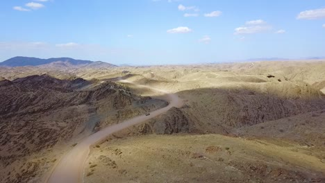 Excellent-Aerial-Of-A-4X4-Jeep-Safari-Vehicle-On-A-Dirt-Road-Through-The-Mountains-Of-The-Namib-Desert-In-Namibia-Africa-1