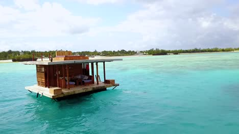 Aerial-Of-A-Woman-Jumping-Off-A-Floating-Gazebo-Into-The-Ocean-In-Tanzania