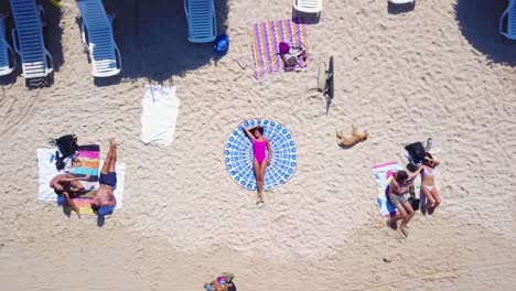 Aerial-Shot-Straight-Down-And-Rising-Of-A-Woman-On-A-Crowded-Beach-In-Cartagena-Colombia