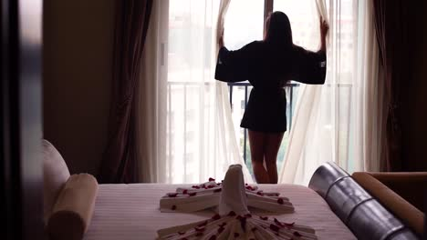 A-Beautiful-Woman-Walks-Up-To-A-Hotel-Resort-Window-And-Opens-The-Curtains