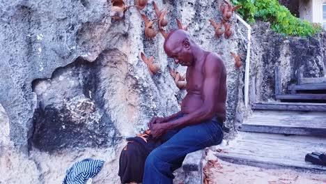 Ein-Alter-Handwerker-Schnitzt-Holz-Besie-Eine-Wand-In-Barbados-Karibik