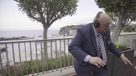 A-Businessman-In-A-Suit-Dances-On-The-Street-With-Headphones-And-A-Group-Of-Young-People-In-Monaco