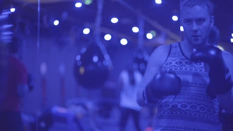 A-Boxer-Works-Out-With-A-Punching-Bag-In-A-Blue-Neon-Lit-Gym