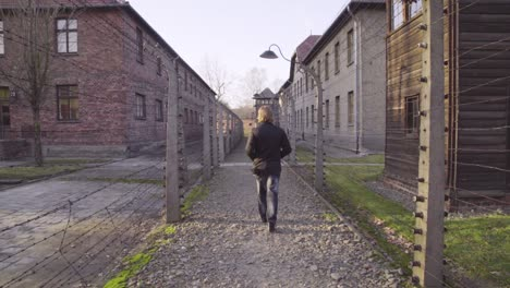 A-Man-Walks-Through-A-Barbed-Wire-Corridor-At-Auschwitzbirkenau-Nazi-Concentration-Camp-Poland