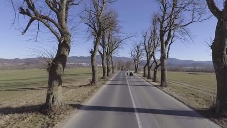 A-Man-And-Woman-Run-Down-The-Middle-Of-A-Road-In-Slovenia-In-This-Drone-Aerial-Shot