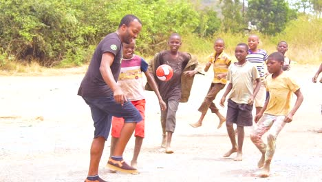 African-Kids-Play-Soccer-Football-On-A-Dirt-Field-With-Brothers-And-Fathers-In-Slow-Motion