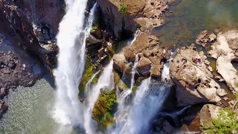 Antena-De-Un-Hombre-Y-Una-Mujer-Sentados-En-La-Cascada-De-La-Piscina-Del-Diablo-En-Victoria-Falls-Zambia-2