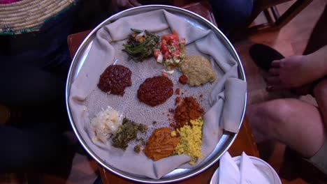 Slow-Motion-Of-Hand-Opening-Basket-Containing-Traditional-Ethiopian-African-Injera-Food-On-A-Silver-Tray