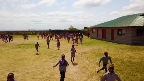 Drone-Shot-Of-Children-Running-At-An-Orphanage-Or-School-In-Rural-Kenya