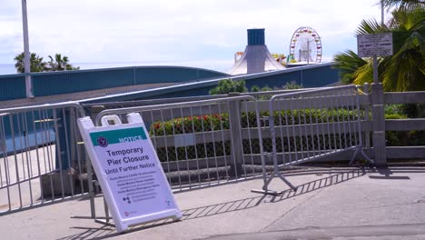A-Sign-Indicates-The-Santa-Monica-Pier-Is-Closed-During-Covid19-Corona-Virus-Outbreak-Epidemic
