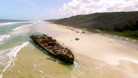 People-approach-an-old-shipwreck-on-a-beach-of-Fraser-Island-off-the-coast-of-Queensland-Australia