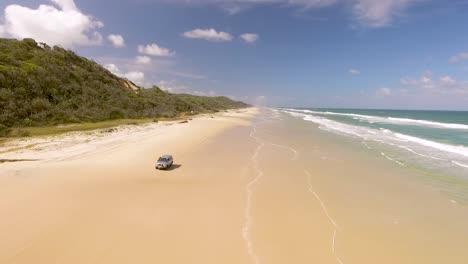 Un-Coche-Conduce-A-Lo-Largo-De-La-Playa-En-Fraser-Island-Frente-A-La-Costa-De-Queensland-Australia
