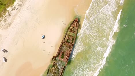 An-aerial-view-shows-people-approaching-an-old-shipwreck-that-has-washed-ashore-on-Fraser-Island-off-the-coast-of-Queensland-Australia